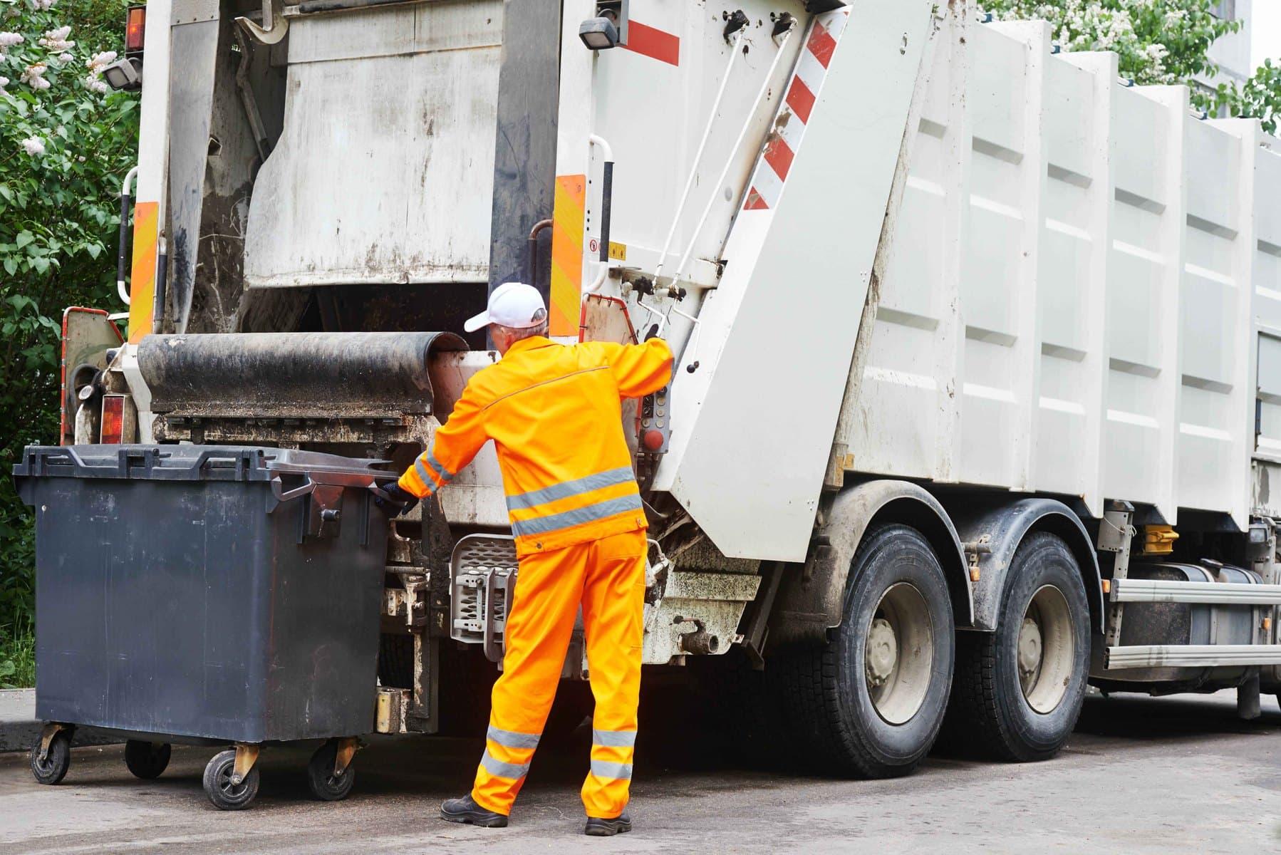 Werknemer van afvaldienst laadt een afvalcontainer in de vrachtwagen.